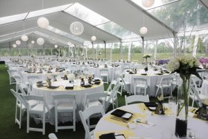 An image from within a setup clear span tent of dozens of round tables with 10+ chairs per table in a tent with no tent polls inside and transparent panels in the ceiling of the tent to allow natural light in, spacious and beautiful for an event.
